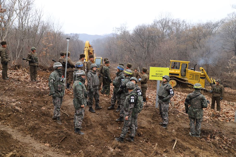 A South Korean, right, and a North Korean shake hands as the two Koreas start building a road inside the Demilitarized Zone in Cheorwon, Gangwon Province, Thursday. Yonhap