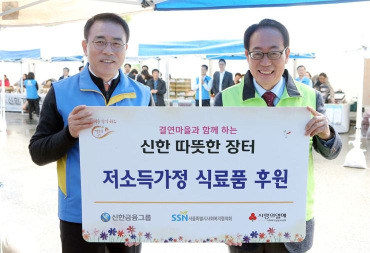 Shinhan Financial Group Chairman Cho Yong-byoung, left, holds up an agreement to provide agricultural goods to low-income households in front of Shinhan Bank in Seoul, Thursday. Employees from the group and its subsidiaries such as bank, credit card and securities units opened a pop-up market to promote and sell farmers' agricultural products. Courtesy of Shinhan Financial Group