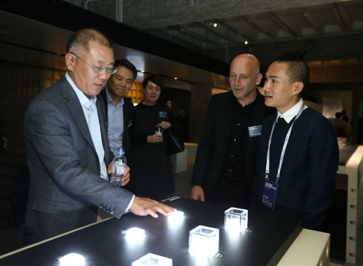 Hyundai Motor Group Executive Vice Chairman Chung Eui-sun, left, listens to an explanation about 'Cillia,' an art piece by Chinese artist Ou Jifei, right, during the opening ceremony of the 'Future Humanity-Our Shared Planet' exhibition at Hyundai Motorstudio Beijing, Wednesday. Courtesy of Hyundai Motor