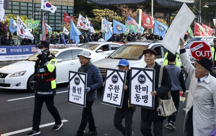Members of civic groups stage a protest at Gwanghwamun in Seoul, Saturday, urging the withdrawal of U.S. forces from Korea on the occasion of Student Day. in the back ground can be seen people who participated in a 'Taegeukgi rally' calling for the enhancement of the Korea-U.S. alliance. Yonhap