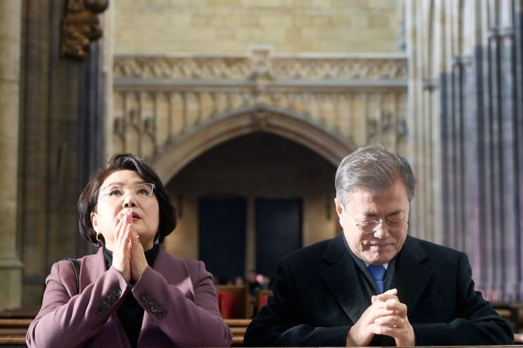 President Moon Jae-in prays at St. Vitus Cathedral in Prague, Czech Republic, during his recent visit on the way to Argentina for the G20 summit. At his side is first lady Kim Jung-sook. Yonhap