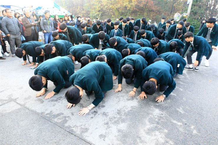 High school juniors and sophomores bow for success for seniors who take the College Scholastic Ability Test at Sokcho High School in Gangwon Province, Thursday. Yonhap