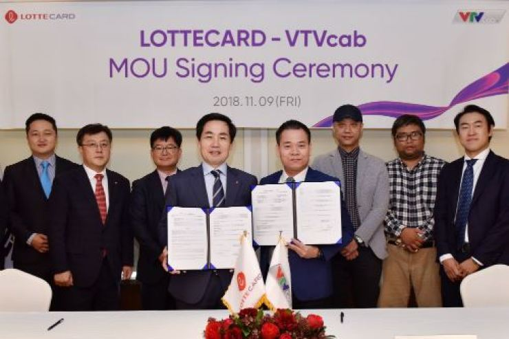 Lotte Card CEO Kim Chang-kwon, fourth from left, shows an MOU agreement for business partnership with Vietnam's VTV Cab Chairman Hoang Ngoc Huan, fourth from right, at Lotte Hotel in central Seoul, Nov. 9. / Courtesy of Lotte Card