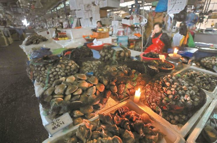 Fishmongers sell seafood by candlelight at the old building of Noryangjin Fisheries Wholesale Market in Seoul, Nov. 5, after the National Federation of Fisheries Cooperatives cut power and water amid a conflict with some merchants refusing to move to a new building nearby. / Yonhap