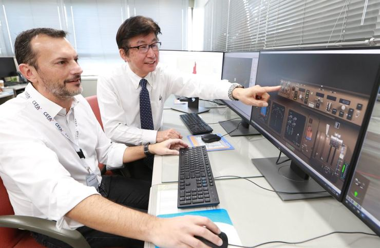 Asiana Airlines Senior Executive Vice President Akiyoshi Yamamura, right, and Carlos Ricarte, director of CEFA Aviation, check an advanced-level Flight Operational Quality Assurance (FOQA) system, Friday. The upgraded system helps the carrier to better analyze different types of flight data. Courtesy of Asiana Airlines