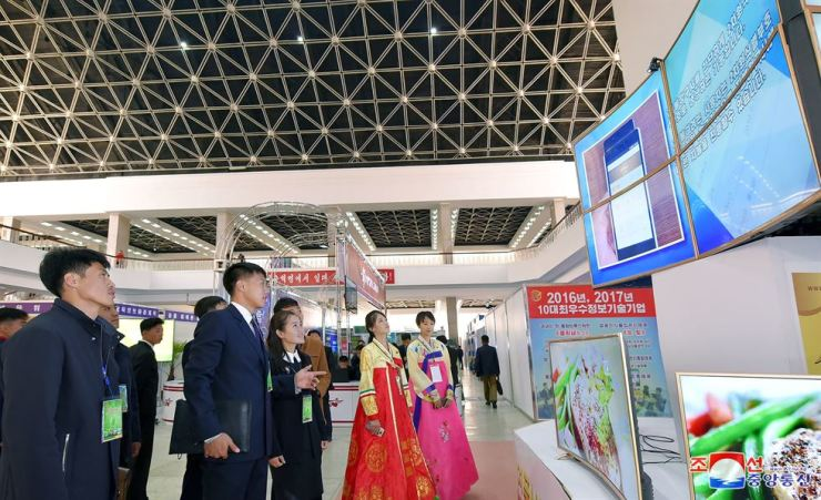 People watch a large screen at the 2018 national exhibition of IT successes at the Three-Revolution Exhibition House in Pyongyang. The Oct. 15-19 exhibition was titled 'The age of knowledge-based economy and IT enthusiasm.' KCNA-Yonhap