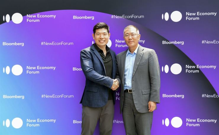 Hyundai Motor Group Executive Vice Chairman Chung Eui-sun, right, shakes hands with Grab CEO Anthony Tan during the Bloomberg New Economy Forum at Capella Singapore, Tuesday. They agreed to boost ties for an electric vehicle-based car-hailing service. / Courtesy of Bloomberg
