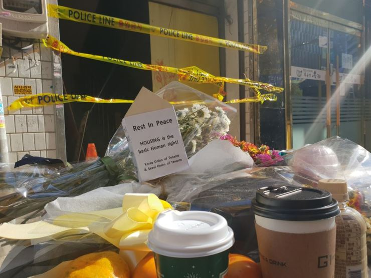 Flower bouquets, tangerines, coffee and other small gifts are left outside the Gukil Gosiwon (a low-cost single-room accommodation) in Jongno, Seoul, Monday, for the seven tenants who died in a fire there Friday. / Korea Times photo by Lee Suh-yoon