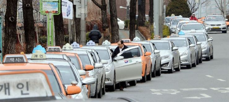 Taxis operated by firms or privately line up near Seoul Station. The city's taxi fares will likely increase by the end of this year. Korea Times file