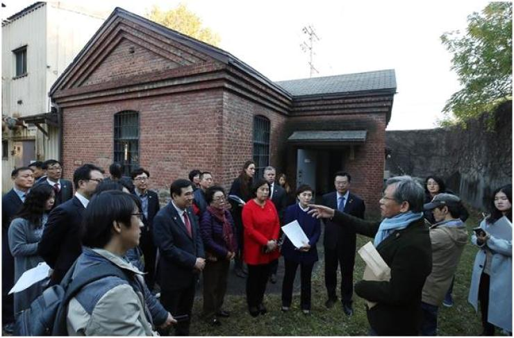 Yoo Hong-jun, former head of the Cultural Heritage Administration, explains the history of U.S. Army Garrison (USAG) Yongsan site in central Seoul, in front of a Japanese military prison building on the compound, during a bus tour, Nov. 2. / Yonhap