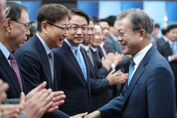 President Moon Jae-in shakes hands with Samsung Vice Chairman Yoon Boo-keun at a meeting to discuss achieving a 'fair economy' held at COEX in southern Seoul, Friday. / Yonhap