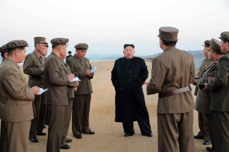 North Korean leader Kim Jong-un, center, speaks to military officials at an unspecified national defense institute in this photo that appeared in the North's state newspaper Rodong Sinmun 's Friday edition. / Yonhap