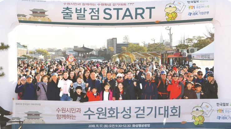 Walkathon in Hwaseong Fortress: Participants in the 480th Turtle Marathon, hosted by Hankook Ilbo newspaper, gesture at the starting point at Hwaseong Fortress' Haeng Palace on Saturday. Suwon City Mayor Yeom Tae-young, Hankook Ilbo President Lee Joon-hee, and ruling party lawmaker Kim Young-jin walked with participants along the fortress. Korea Times photo