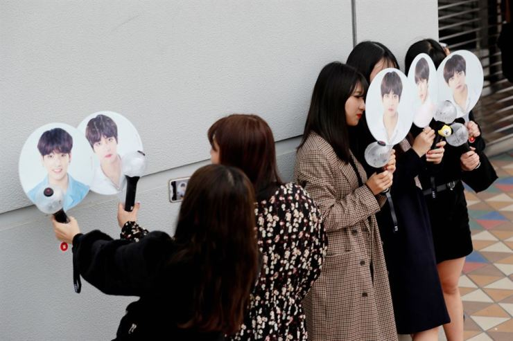 People take their photos with fans bearing photos of the members of South Korean boy band BTS outside Tokyo Dome where the band's concert will be held in Tokyo, Japan, Tuesday.  / Reuters-Yonhap