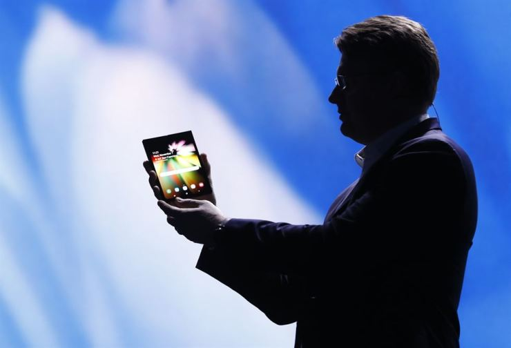 Samsung Electronics Senior Vice President Justin Denison unfolds the company's foldable screen smartphone prototype during the Samsung Developers Conference in San Francisco, Wednesday. / REUTERS-Yonhap