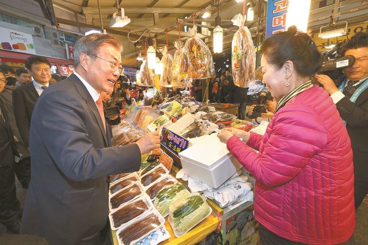 President Moon Jae-in pays for a box of dried mackerel, a specialty of Pohang, North Gyeongsang Province, during a visit to Pohang Jukdo Market, Thursday. Moon visited the southeastern coastal city to attend an inaugural forum on economic cooperation between South Korea and Russia. Yonhap