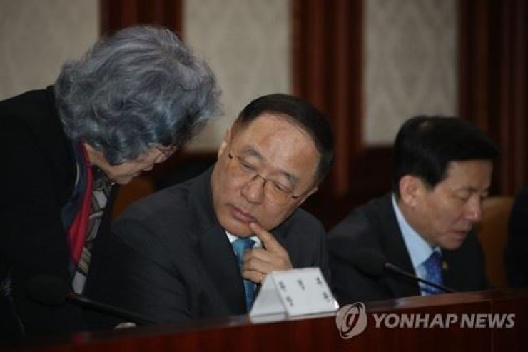 In this March 23 file photo, Hong Nam-ki, center, then head of the Office of Government Policy Coordination, talks with Park Eun-young, head of the Anti-Corruption and Civil Rights Commission earlier this year. / Yonhap