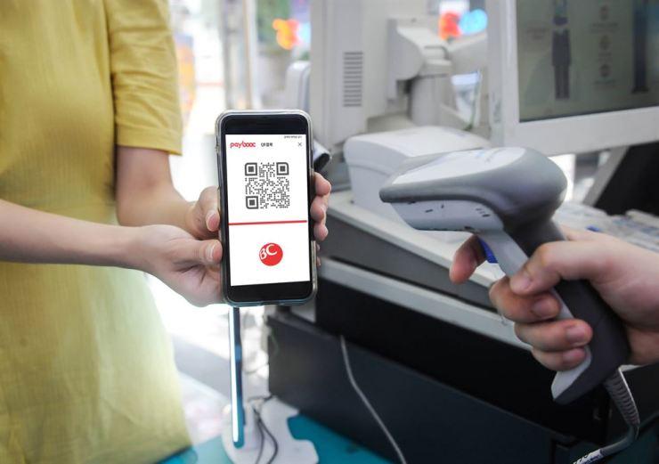 A consumer makes a purchase via a QR code. Korea Times file