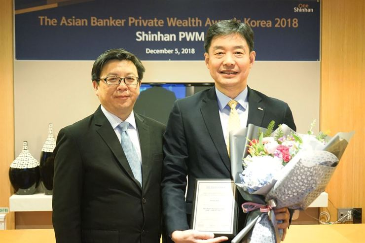 Shinhan Bank Investment Product & Service head Bae Jin-soo, right, holds an award plaque during the Korea Country Award 2018 event at the bank's PWM Privilege Center in Seoul, Thursday. Shinhan Bank was named the nation's best wealth management bank by The Asian Banker for the fourth consecutive year. / Courtesy of Shinhan Bank