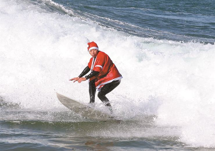 A surfer wearing a Santa suit rides a wave in the waters off the southeastern city of Pohang on Christmas Eve, Monday. Yonhap