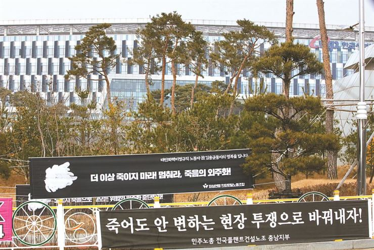 Placards are hung in front of the Korea Western Power (KOWEPO) headquarters in Taean, South Chungcheong Province, Sunday, to urge the state-run company stop outsourcing dangerous jobs to small companies, after a young subcontracted worker, Kim Yong-gyun, was killed after being trapped between conveyer belts, last Tuesday. / Yonhap