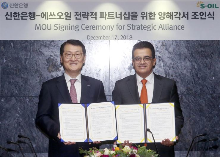 Shinhan Bank CEO Wi Sung-ho and S-Oil Corp. CEO Othman Al-Ghamdi show a memorandum of understanding for a strategic alliance at the firm's headquarters in Mapo, Seoul, Dec. 17. The two agreed to continue their long-term strategic partnership in joint marketing and the launch of new products. Courtesy of Shinhan Bank