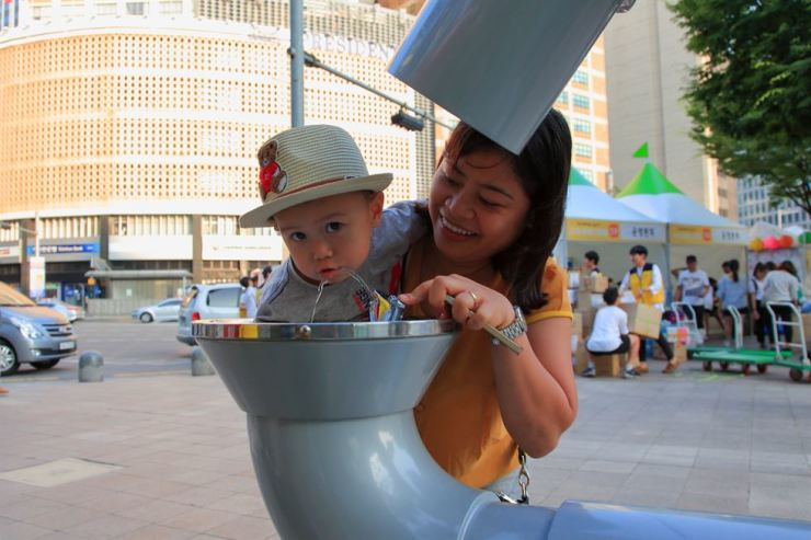 A child drinks from an Arisu fountain in front of City Hall / Courtesy of Seoul Metropolitan Government