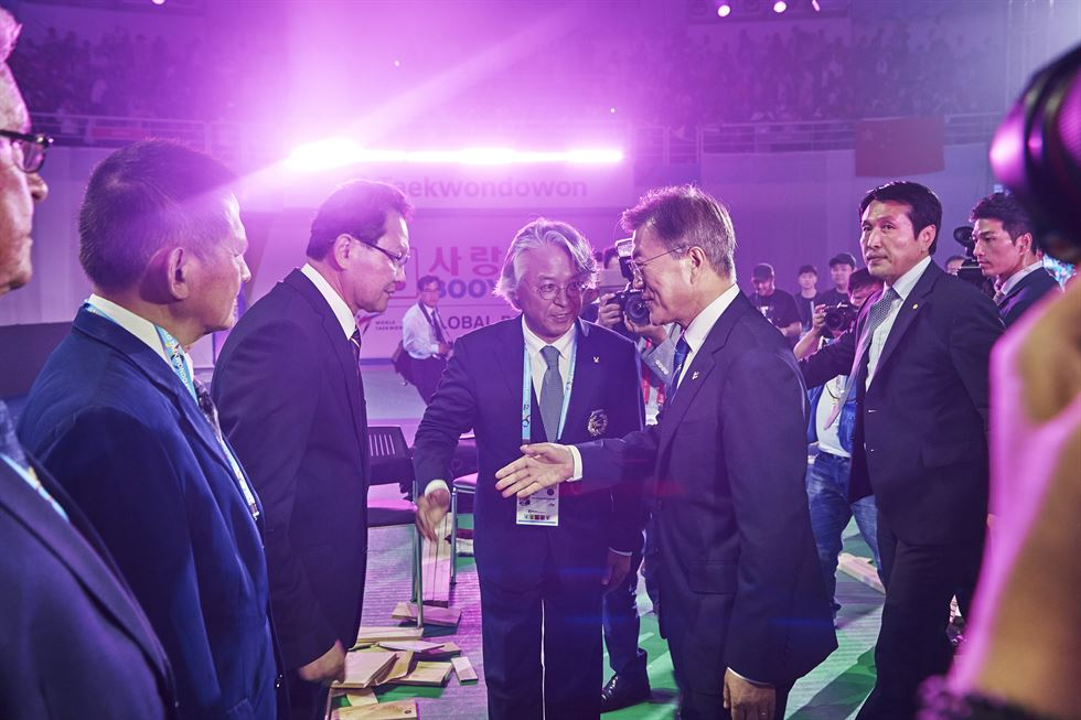 World Taekwondo Executive Deputy Secretary General Kim Eil-chul, center, and North Korea's National Athletics Guidance Committee Chairman Choe Hwi, left, put their palms together as International Taekwondo Federation President Ri Yong-son looks on during a dinner at Okryugwan in Pyongyang on Nov. 2. Courtesy of World Taekwondo