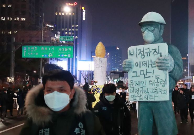 Protesters march near Gwanghwamun Station in central Seoul, Saturday, toward Cheong Wa Dae with a life-size statue of the deceased power plant worker Kim Yong-gyun holding up a sign that says 'No more irregular employment.' / Yonhap
