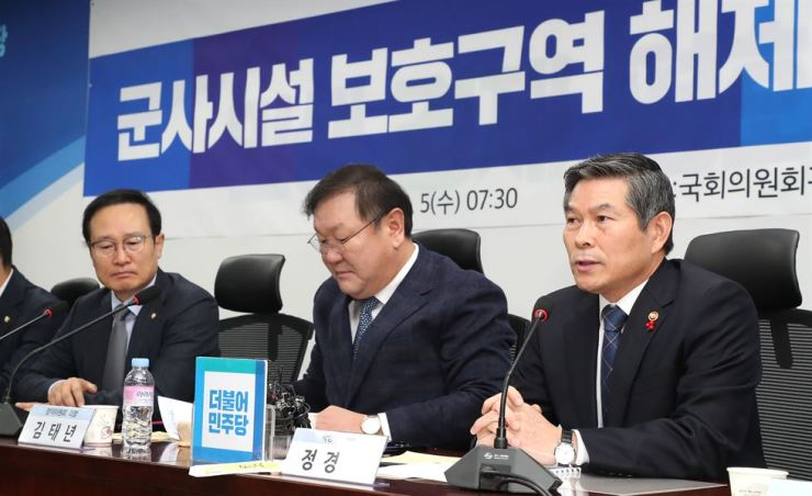 Defense Minister Jeong Kyeong-doo, right, speaks during a consultative meeting with the ruling Democratic Party of Korea (DPK) at the National Assembly, Wednesday. The government and DPK agreed Wednesday to lift some restricted military zones in border areas to ease residents' inconvenience. / Yonhap