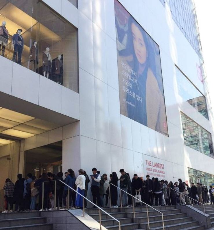 About 150 consumers line up in front of Uniqlo's flagship store in Myeong-dong, downtown Seoul, to buy the Japanese apparel brand's products in this Oct. 12 file photo. / Courtesy of FRL Korea