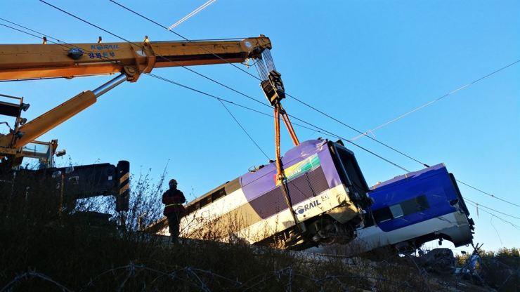 A crane lifts the derailed cars of the KTX train that went off the tracks in Gangneung, Gangwon Province, Saturday, on the way to Seoul. / Yonhap