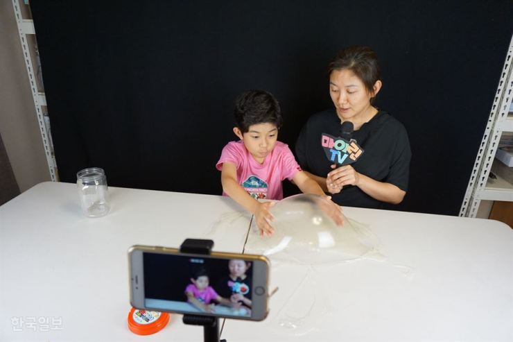 A child who runs Mylynntv on YouTube films a clip with his mother. Online broadcasters, such as 'YouTubers,' have become the fifth-most desired job for elementary schoolchildren. / Korea Times file