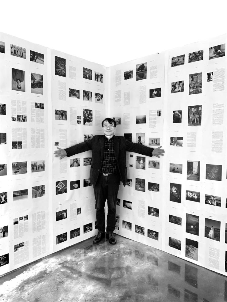 Lee Kyu-sang, founder and publisher of the Seoul-based independent photobook publisher Noonbit Publishing, poses with his arms wide in front of a paper board featuring the timeline of the publishing house's 30-year history at SPACE 22 in southern Seoul in November. Courtesy of Byun Soon-cheol