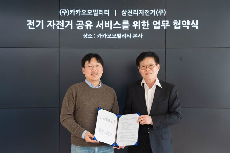 Kakao Mobility CEO Jung Joo-hwan, left, poses with Samchuly Bicycle CEO Shin Dong-ho after signing a business agreement to launch an electric bike-sharing service. / Courtesy of Kakao Mobility