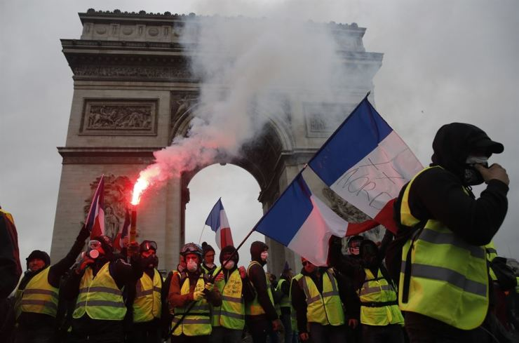 Protesters wearing yellow vests (gilets jaunes) wave flares and French flags near the Arc de Triomphe during a demonstration over high fuel prices on the Champs-Elysee in Paris on Dec. 1. EPA