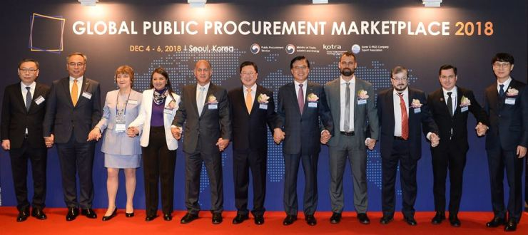 Public Procurement Service head Park Chun-sup, sixth from right, and Korea Trade-Investment Promotion Agency CEO Kwon Pyung-oh, fifth from right, hold hands with other guests during the Global Public Procurement Marketplace 2018 event at the Grand Intercontinental Hotel in Seoul, Tuesday. / Courtesy of Korea Trade-Investment Promotion Agency
