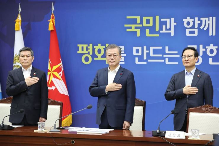 President Moon Jae-in salutes the national flag before the start of a briefing on the defense ministry's policies for next year, held at its headquarters in Yongsan, Seoul, Thursday. At left is Defense Minister Jeong Kyeong-doo, and right, Hong Young-pyo, the ruling Democratic Party of Korea floor leader. Yonhap