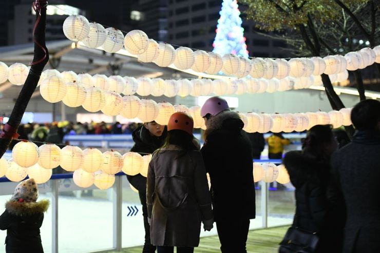 Visitors leave messages on lanterns at the ice skating rink at Seoul Plaza last year. / Courtesy of Seoul Metropolitan Government