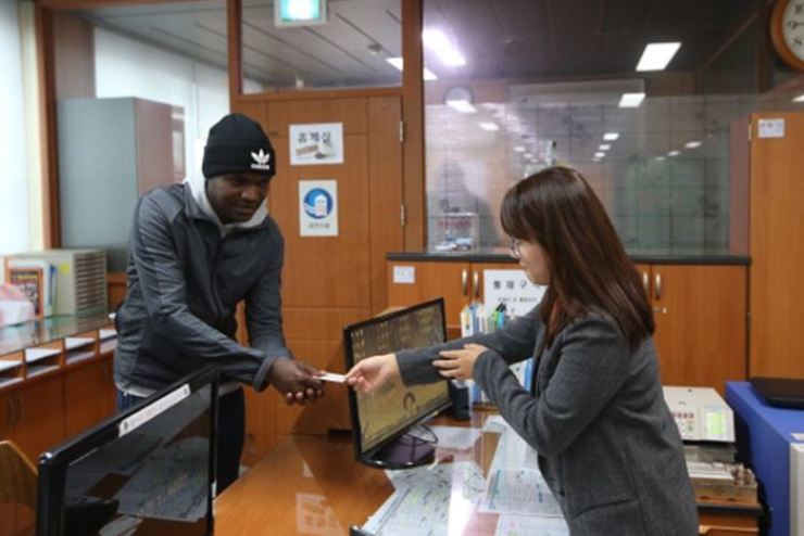 Kenyan-born marathoner Oh Joon-han receives a new ID card from a community center in Cheongyang County, South Chungcheong Province, after legally changing his name from Wilson Loyanae Erupe. / Korea Times file