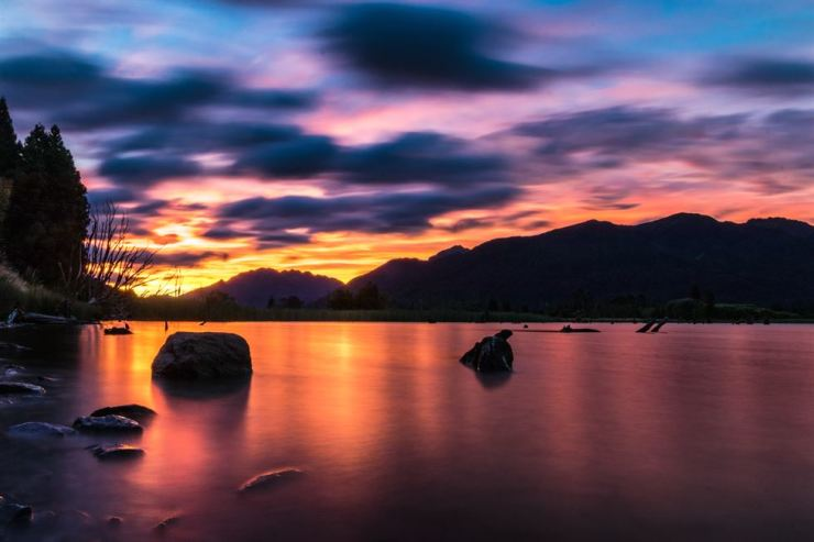 A colorful sky and mountains above a tranquil bay at sundown in New Zealand. gettyimagesbank
