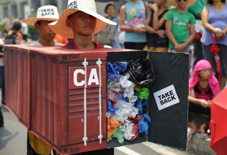In this May 7, 2015, file photo, Filipino environmental activists wear a mock container filled with garbage to symbolize the containers of waste that were shipped from Canada to the Philippines, as they protest outside the Canadian Embassy in Manila. AP