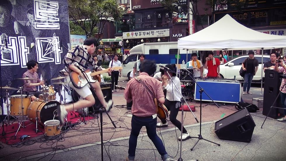 Wasted Johnnys play in the rain at Washington Square Park at a 2014 concert in support of North Korean refugees, as seen in the 2017 documentary film 'Life Is a Dream We'll Wake Up & Scream.' / Courtesy of Joe Je-hwan