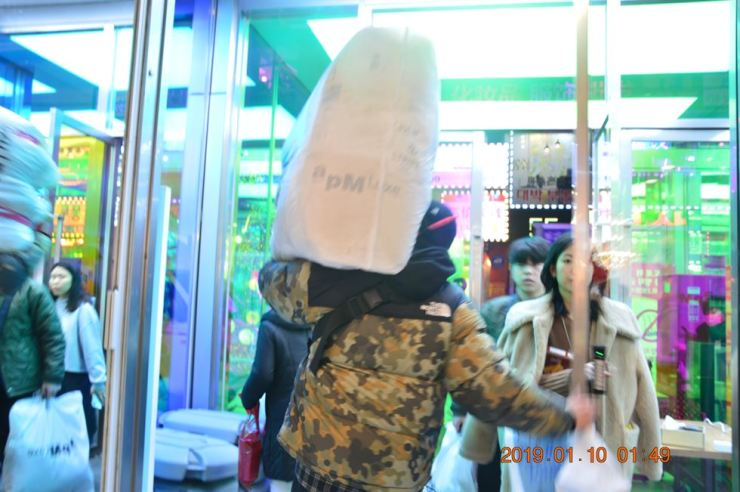 A 29-year-old 'Purchasing uncle' Hwang Jung-ho carries a huge vinyl bag stuffed with clothes, after visiting a number of shops in Dongdaemun, Seoul, Wednesday. Korea Times photo by Kang Aa-young.