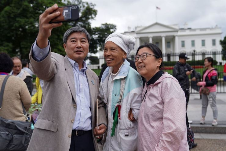 H. K. Suh, Korean-American, Lucy Murphy and Kate Shim, also Korean-American, take a selfie during a vigil outside the White House to celebrate the joint summit between U.S. President Donald Trump and North Korean leader Kim Jong Un held in Singapore, in Washington, U.S., June 11, 2018. Yonhap