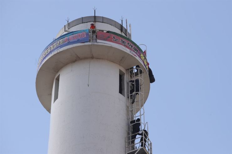 The labor union of FineTek reached a labor deal Friday, while two workers staged a sit-in on top of a 75-meter smokestack at a power plant for more than a year in protest of layoffs. Yonhap