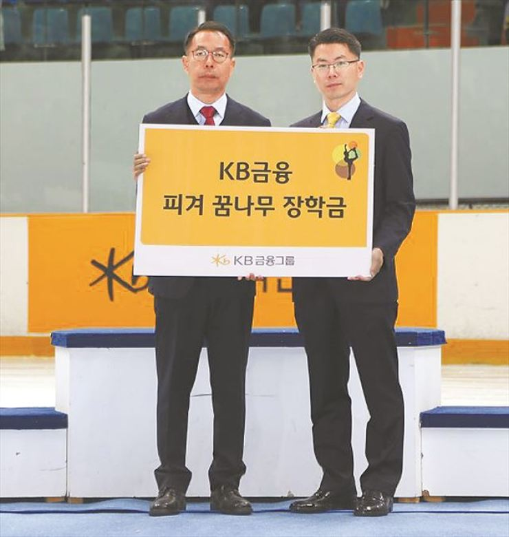 KB Financial Group General Manager Moon Seung-chul, right, donates 50 million won to the Korean Skating Union at an ice rink in Mokdong, southwestern Seoul, Monday. The donation will be used to help pay for local figure skaters' school tuitions. The group has been supporting figure skaters since 2006 when it started to back Olympic gold medalist Kim Yuna. Courtesy of KB Financial Group