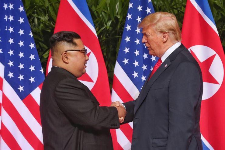 North Korean leader Kim Jong-un and U.S. President Donald Trump shake hands at their historic summit at the Capella Resort in Singapore, June 12. / Korea Times file