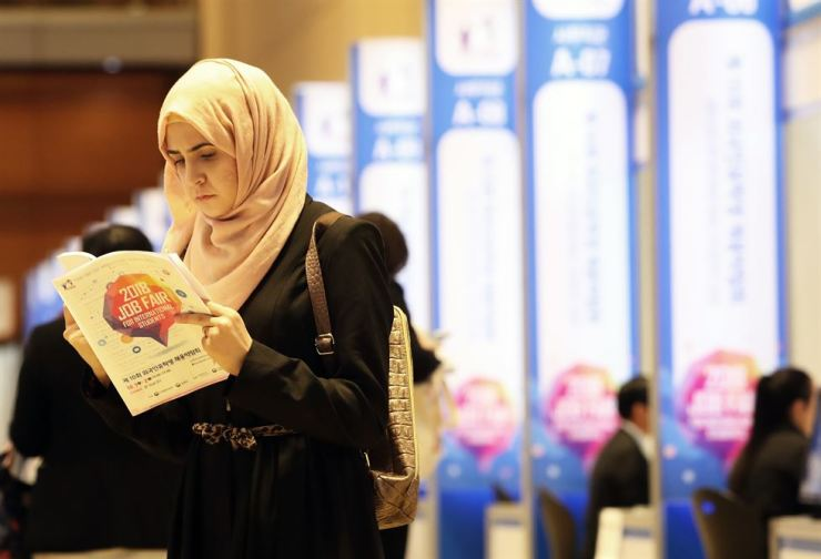 A visitor to '2018 Job Fair for International Student,' hosted by the Korea Trade-Investment Promotion Agency at COEX in Gangnam-gu, Seoul, checks a booklet in October 2018. News1