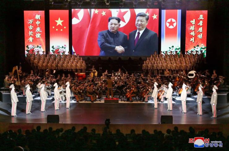 North Korea's leader Kim Jong-un and Chinese President Xi Jinping feature on a big screen during the North Korean art troupe's performance at the Chinese National Center for the Performing Arts in Beijing. The troupe performed from Jan. 26-28. KCNA-Yonhap